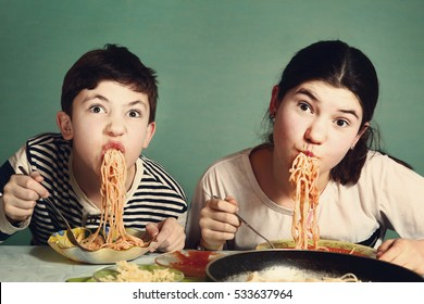 happy teen siblings boy and girl eat spaghetti together hanging from mouth grimacing happily.