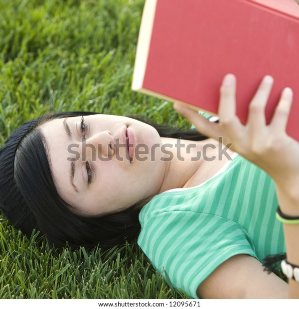 Happy teen studies with book in the grass