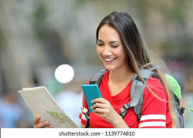 Happy teen tourist consulting online information on a smart phone walking on the street