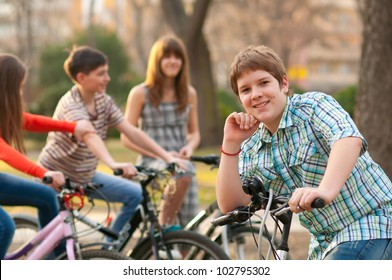 Happy teenage boy spending time with his friends riding bicycles.