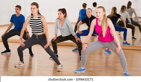 happy teenage boys and girls learning to dance in dance hall