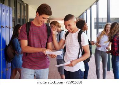 Happy teenage boys sharing exam results in school corridor