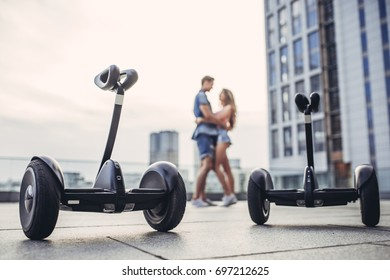 Happy teenage couple is having fun in the city. Young man and woman near gyro scooters.
