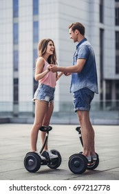 Happy teenage couple is having fun in the city. Young man and woman on gyro scooters.