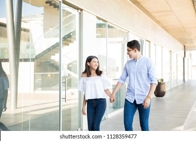Happy teenage couple holding hands while walking in corridor at mall