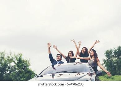 Happy teenage friends having fun sit on car along country road.
