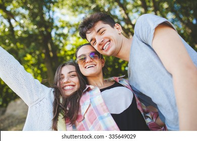 Happy teenage friends smiling outdoors on nature. Handsome young people having fun together and posing for camera.
