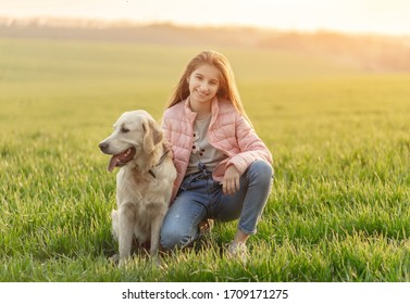 Happy teenage girl with cute dog on green spring grass