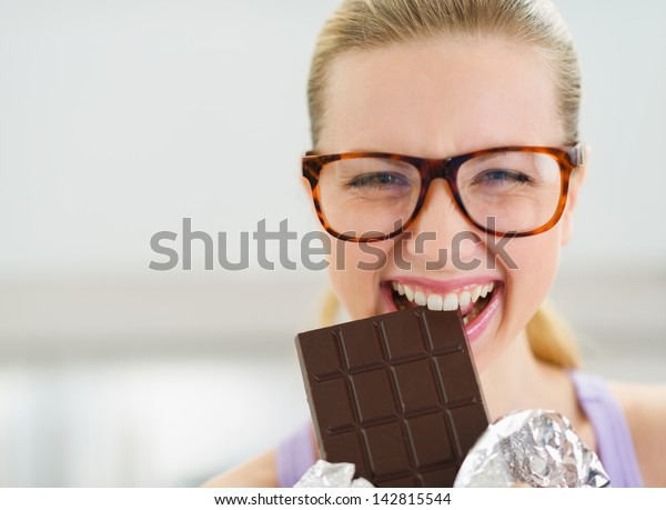 Happy teenage girl eating chocolate bar