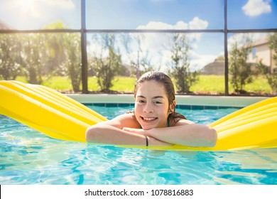 Happy Teenage girl floating in an outdoor swimming pool. Carefree, fun, happy portrait of a hispanic girl smiling and enjoying a day in the sun floating on an inflatable raft
