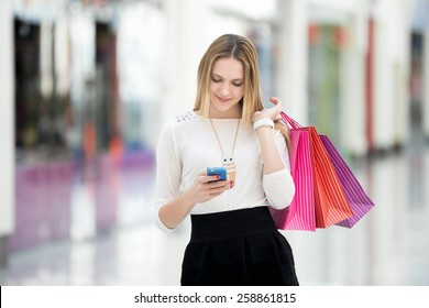 Happy teenage girl holding bags with purchases, smiling while looking at phone in shopping center. Received good news, reading message, texting, dialing number, using app on smartphone