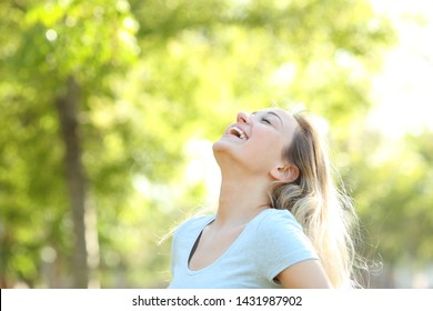 Happy teenage girl laughing and breathing fresh air in a park or forest