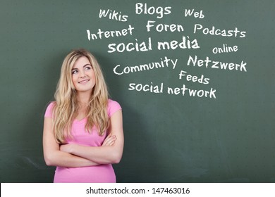 Happy teenage girl looking at collection of social media and networking related words on blackboard