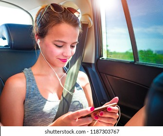A happy teenage girl looking at the ecre of his smartphone while sitting in a van wearing headphones.