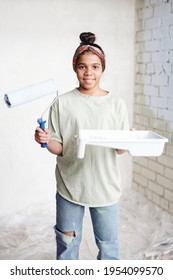 Happy teenage girl with paintroller and white container with paint standing in front of camera against corner by two walls of living-room