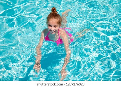 Happy teenage girl in pink swimsuit swimming in blue transparent water in swimming pool at aquapark