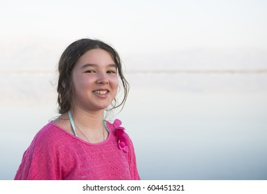 Happy teenage girl in pink t-shirt at lake background