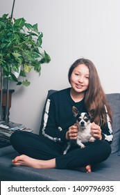 Happy teenage girl with a puppy.  Girl have fun with her dog in house. Dog owner having fun with pet at home. Concept human and pets. Friendship between human and dog. Teenager with Dog. Brace face.