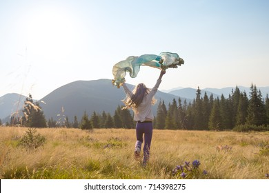 Happy teenage girl runs along the alpine meadow with a waving scarf in her hands. Amazing travel in a wilderness. Back view, back light.