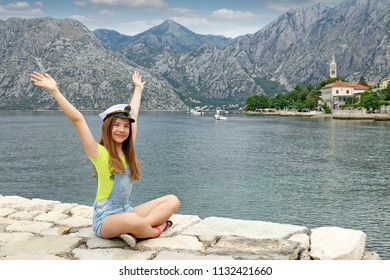 happy teenage girl with sailor hat and hands up on summer vacation