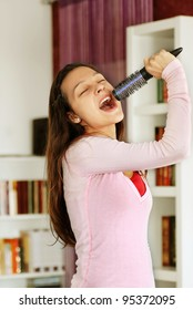 happy teenage girl singing with a hairbrush