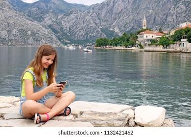 happy teenage girl sitting near sea and having fun with smart phone
