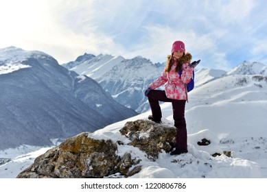 Happy teenage girl standing on a stone smiling in snowy mountains in winter.