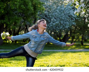 Happy teenage girl in the sunlight. Emotions - happiness, joy. Woman laughing happily. Park dawn. Flowers of apple, apple orchard. Girl dancing, jumping