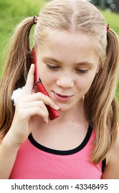 Happy teenage girl talks on cellural phone on green grass background