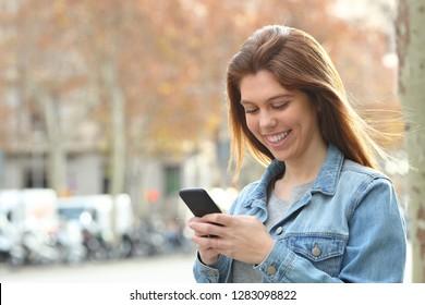Happy teenage girl texting on smart phone walking in the street