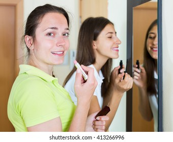 Happy teenage girlfriends having fun while putting make up near of a mirror