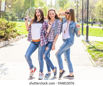 Happy teenage girls having fun in summer sunny park. Spring hot weather