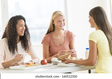 Happy teenage girls having snacks in university canteen
