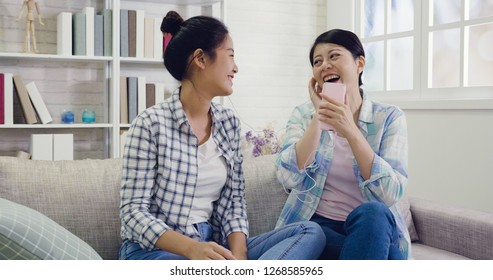 Happy teenage girls listening to music having fun together at home. young asian girls wearing earphones enjoy the songs sitting on couch relaxing at home on weekends. best friends chill out indoors.