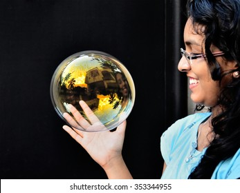 Happy teenage Indian girl with a large colorful soap bubble against black background.