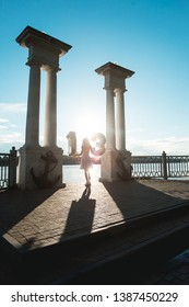 Happy teenage party girl 12-13 years old with balloons. Standing on the lake side between columns in sunflare
