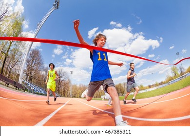 Happy teenage sprinter coming first to finish line