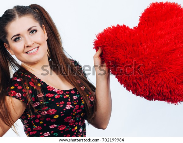 Happy teenage woman holding heart shaped pillow. Valentines day gift ideas concept.