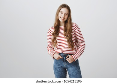 Happy teenage years. Portrait of young pretty blonde girl in trendy striped sweater holding hand in pocket and smiling broadly, feeling shy and timid, standing over gray background