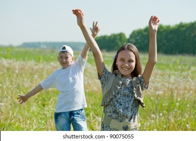 Happy  teenager boy and girl together at meadow in summer