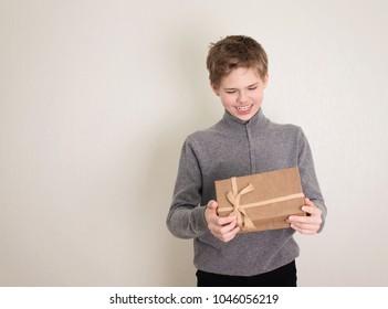 Happy teenager boy opening his present.
