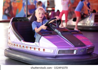Happy teenager boy rides electric car during fan-fair entertainment