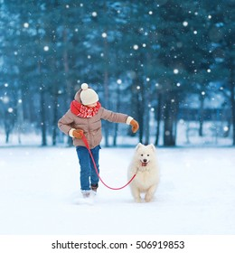 Happy teenager boy running playing with white Samoyed dog on snow in winter day, flying snowflakes
