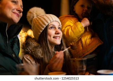 Happy teenager enjoying traditional food at Christmas market in Zagreb, Croatia.