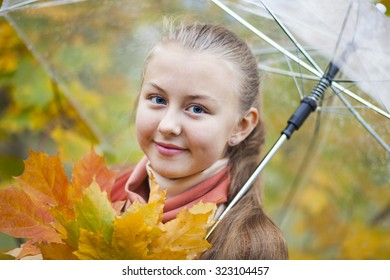 Happy teenager with fall leaves and umbrella in autumn park