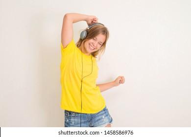Happy teenager girl in headphones dancing and listening to music.