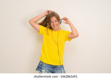 Happy teenager girl in headphones listening to music.