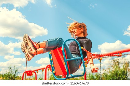 Happy teenager girl on a swing. Sky in the background