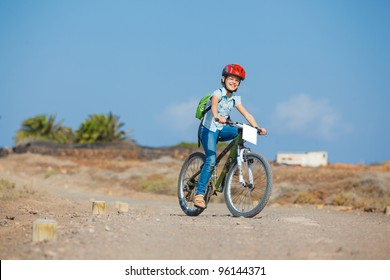 Happy teenager girl over a bicycle and looking the view, on a road