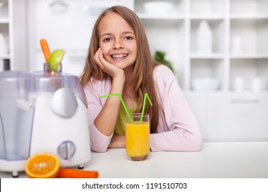Happy teenager girl sitting in the kitchen with a fresh squeezed fruit juice - showing a broad smile